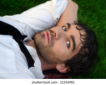 Close-up portrait of young good looking man in white shirt against grass