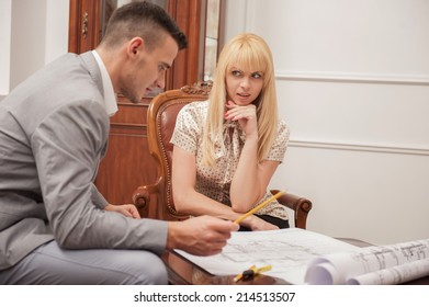 Close-up portrait of young handsome architect discussing ground plan with client sitting at the table in design studio,  pointing at architectural plan with pencil, creative discussion concept