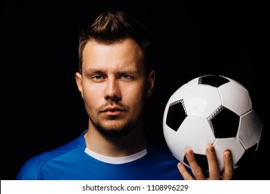 Close-up portrait of young handsome football player soccer posing on black dark background and holds the ball in his hand. Blue outfit. Bristles, blue eyes.