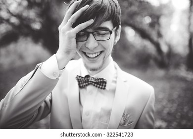 close-up portrait of a young handsome guy groom delectable hipster in a suit and bow tie on a background autumn forest smiling and posing with glasses