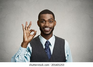 Closeup portrait young handsome, happy, smiling, excited man, corporate employee, worker giving OK sign with fingers, isolated black grey background. Positive human emotion facial expressions, symbol