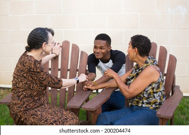 Closeup portrait, young handsome man having conversation with family sitting down, isolated outdoors background