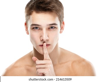 Close-up portrait of young handsome man quiet gesture with finger isolated on white background