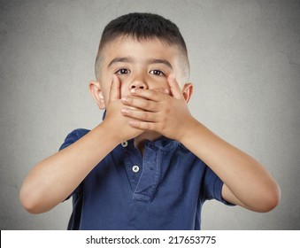 Closeup portrait young handsome man, boy closing, covering mouth with hands can't speak hiding isolated grey wall background. Speak no evil concept. Human emotion facial expression feeling reaction