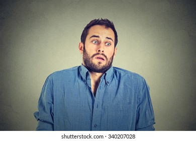 Closeup portrait young handsome man shrugging shoulders who cares so what I don't know gesture isolated on grey wall background. Body language expression. Man showing ignorance