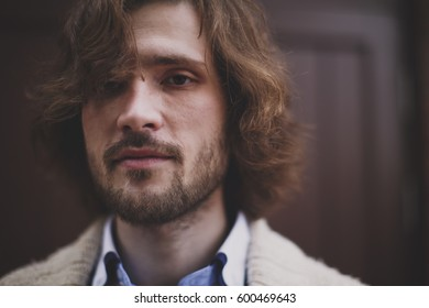 Close-up portrait of young handsome man with dark flowing hair