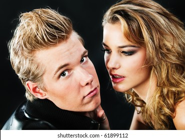 Closeup portrait of young handsome man and pretty woman in darkness