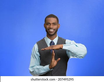 Closeup portrait young, happy, smiling, executive company man showing time out gesture with hands, isolated blue background. Positive human emotion, facial expression feelings, body language attitude