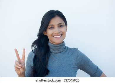 Closeup portrait, young, happy, smiling, confident, excited woman giving peace victory, two sign gesture, isolated white wall background. Positive emotion facial expression feelings symbols, attitude