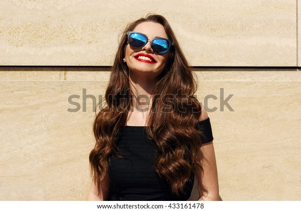 Closeup portrait of young happy smiling beautiful girl with long brunette curly hair posing against wall and smiling on a sunny warm day