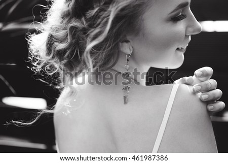 close-up portrait of a young happy sweet slim sexy young curly blonde woman in white lace lingerie morning bride on a sunny day on the green porch smiling and posing lifestyle in earring