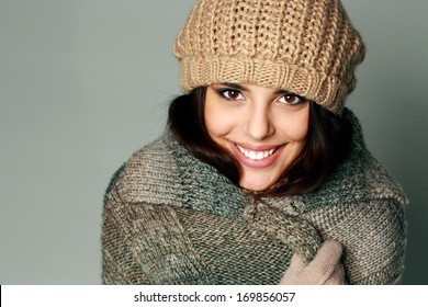 Closeup portrait of a young happy woman in warm winter outfit on gray background