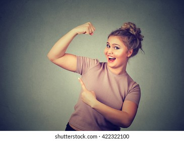 Closeup portrait young happy woman flexing muscles showing her strength isolated on grey wall background. Positive emotion facial expression feeling attitude perception wellbeing. Weight loss concept