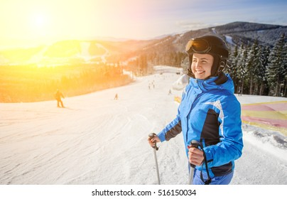 Close-up portrait of young happy woman skier looking at beautiful mountain landscape at the ski resort on a sunny day. Girl is wearing blue jacket helmet and goggles. Wide angle. Bukovel, Ukraine