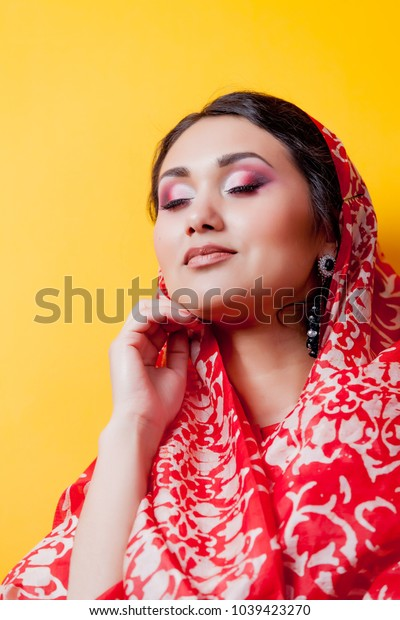 Closeup portrait of young indian girl in sari on yellow background