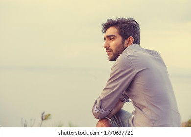 Closeup portrait of young Indian man on sunset thinking, sitting on a mountain rock by the sea and looking at sunset.