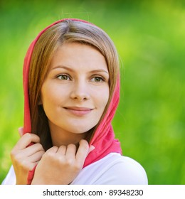 Close-up portrait of young joyous beautiful blonde woman wearing red headscarf and looking somewhere at summer green park.
