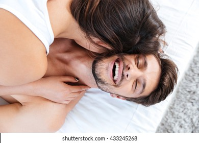 Close-up portrait of a young laughing couple in bed at home