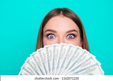 Close-up portrait of young lovely nice sweet excited crazy girl lady, covering face with fan of hundreds USA dollars. Isolated over bright vivid teal turquoise background