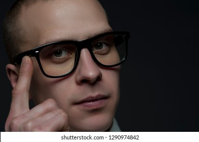 Close-up portrait of a young male businessman with glasses pointing his head. Concept think and develop. Copyspace