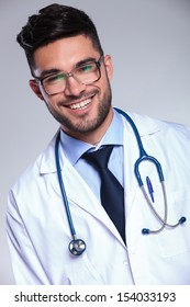 closeup portrait of a young male doctor smiling for the camera. on gray background