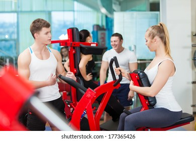 Close-up portrait of a young male gym instructor helping an young woman