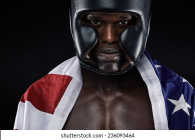 Close-up portrait of young male wearing boxing helmet with american flag against black background