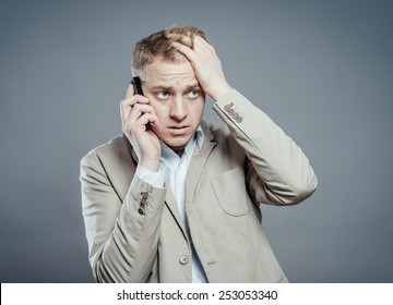 Closeup portrait, young man annoyed, frustrated, pissed off by someone listening on his mobile phone, bad news. Long wait times, horrible conversations concept