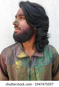 Closeup portrait of young man covered with multicolor holi color powder and standing against white wall, Bearded and long haired Indian guy celebrating Holi festival and looking his right side