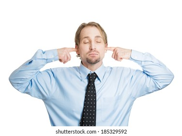 Closeup portrait, young man, covering closed ears, annoyed by loud noise or ignoring someone, not wanting to hear their side of story, isolated white background. Negative human emotion