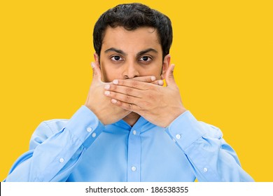 Closeup portrait, young man covering closed mouth and eyes. Speak no evil concept, isolated yellow background. Negative human emotion facial expressions signs and symbols. Media news coverup