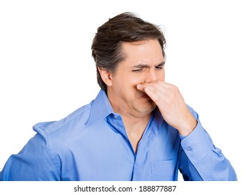 Closeup portrait, young man, disgust on his face, pinches his nose looks away, something stinks, very bad smell, situation, isolated white background. Negative emotion facial expression feeling