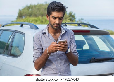 Closeup portrait young man driver next to his black car and checking his phone, annoyed by navigation gps system or bad text message or email, isolated outdoors background