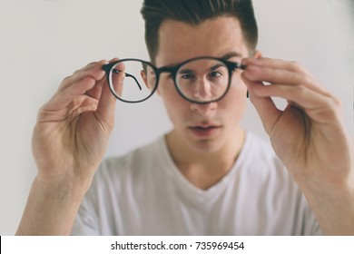 Closeup portrait of young man with glasses.  Handsome guy is holding his eyeglasses right in front of camera with one hand. The concept is isolated on a white background.