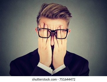 Closeup portrait young man in glasses covering face eyes with both hands isolated on gray wall background