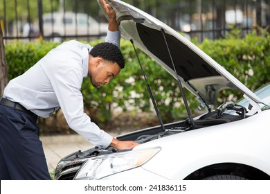 Closeup portrait, young man having trouble with his broken auto, opening hood trying to fix engine, isolated green trees outside background. Car won't start, dead battery