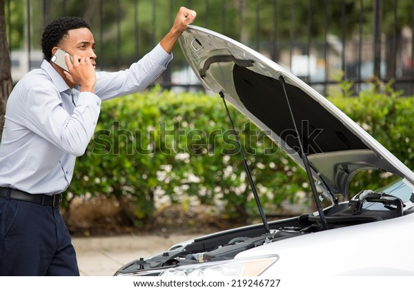 Closeup portrait, young man having trouble with his broken car, opening hood and calling for help on cell phone, isolated green trees outside background
