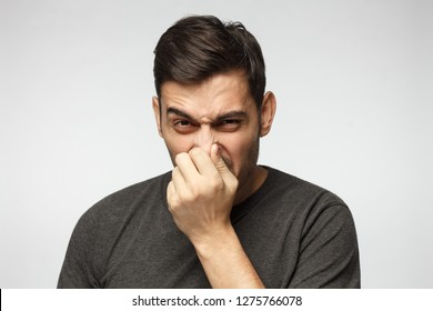 Close-up portrait of young man holding his nose as if smelling something rotten and stinky, trying to find source of odor