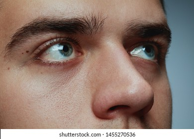 Close-up portrait of young man isolated on grey studio background. Caucasian male model's face and blue eyes. Concept of men's health and beauty, self-care, body and skin care, phycology. Looks calm.