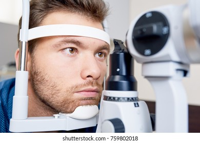 Closeup portrait of young man  looking at slit lamp machine, resting head on stand during sight testing in optometrist office