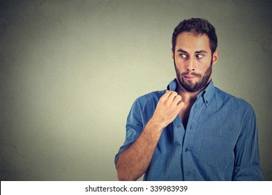 Closeup portrait, young man opening shirt to vent, it's hot, unpleasant, Awkward Situation, Embarrassment. Isolated on gray background. Negative emotions facial expression, feelings