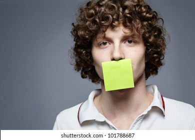 Closeup portrait of young man with a piece of paper covering his mouth on gray background