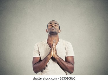 Closeup portrait young man praying hands clasped hoping for best asking for forgiveness or miracle isolated gray wall background. Human emotion facial expression feeling