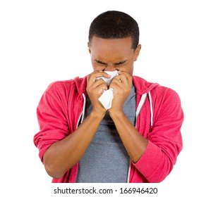 Closeup portrait of young man in red hoodie with allergy or cold, blowing his nose with a tissue, looking miserable unwell very sick, isolated on white background. Flu season and vaccination.