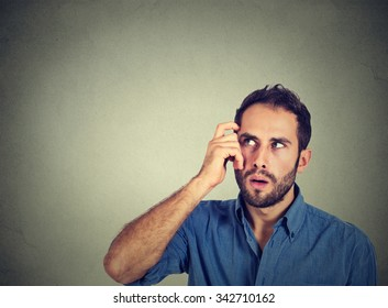 Closeup portrait young man scratching head, thinking deeply about something, looking up, isolated on grey wall background. Human facial expression, emotion, feeling, sign body language