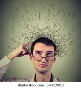 Closeup portrait young man scratching head, thinking daydreaming with brain melting into many lines question marks looking up isolated on gray background. Human facial expression emotion feeling sign