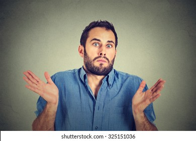 Closeup portrait young man shrugging shoulders who cares so what I don't know gesture isolated on grey wall background. Body language