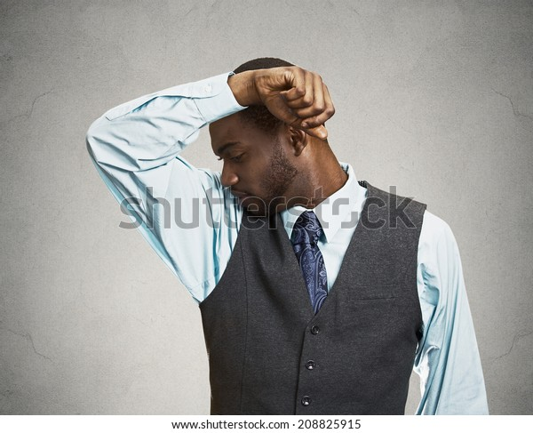 Closeup portrait young Man, Smelling sniffing Armpit, something Stinks very bad, foul Odor situation isolated grey, black background. Negative human emotions, facial expressions, feeling body language