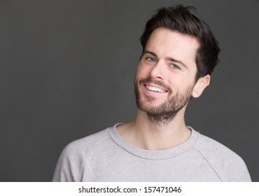 Closeup portrait of a young man smiling on isolated gray background
