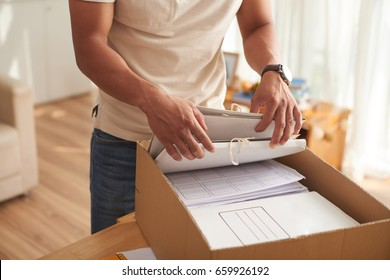 Closeup portrait of young man sorting financial documents in paper folders at home